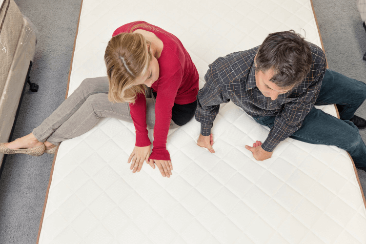 a couple checking the firmness level of a mattress