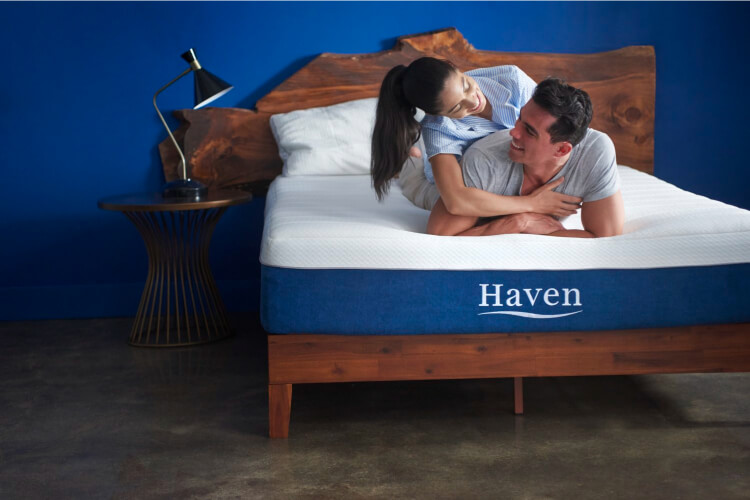 a couple laying on a Haven Mattress Bed