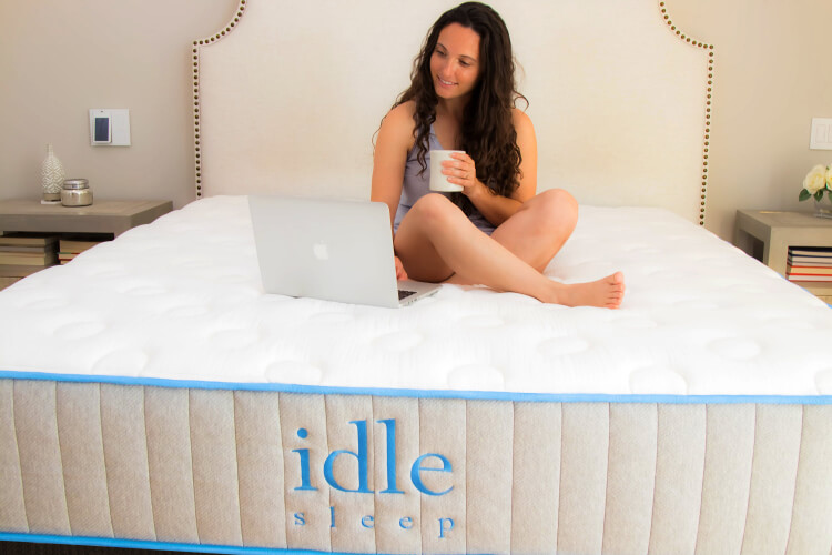 A woman sitting on the Idle Sleep Gel Plush mattress